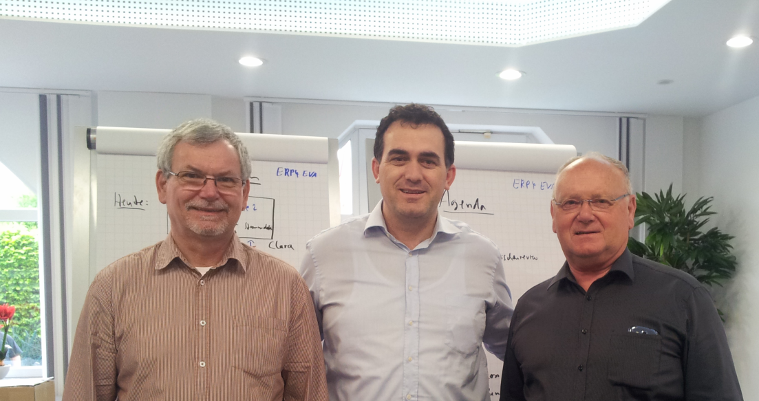 Mr. Hajrizi in the middle , with two representatives of the workshop and the assessment team